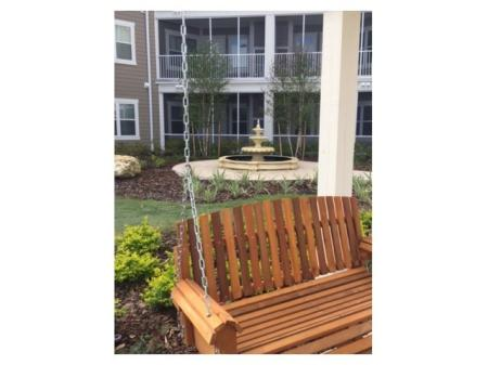Zen courtyard with a large wooden swing, fountain, and green space l Monterey Pointe