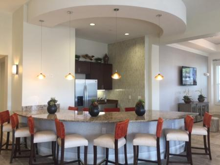 A series of chairs arranged around a built-in kitchen island with refrigerator and kitchen area l Monterey Pointe