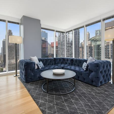 Model living room with wood flooring and a city view through the floor-to-ceiling windows