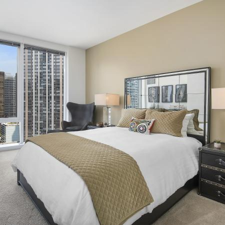 Furnished bedroom with queen sized bed, carpeted floors and floor-to-ceiling windows with a city view