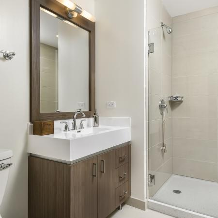 Model bathroom with framed vanity mirror and walk-in shower