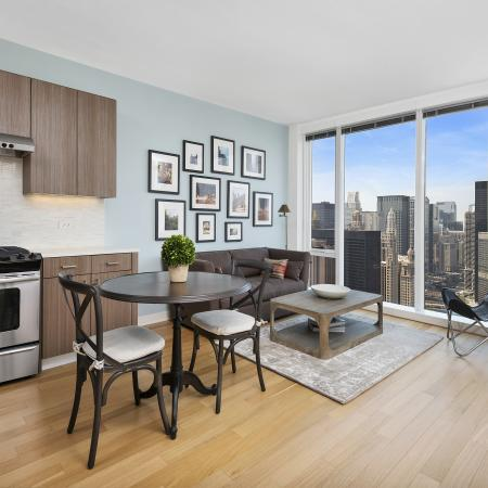 Furnished kitchen and dining room with stainless steel appliances, wood flooring and floor-to-ceiling windows with a city view