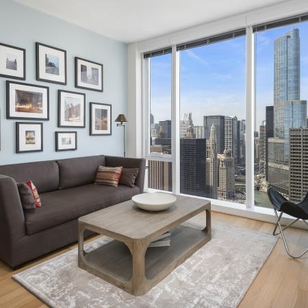 Furnished living room with wood flooring and floor-to-ceiling windows with a city view