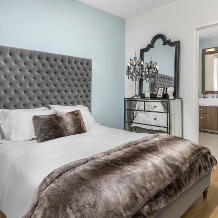 Furnished model bedroom with queen sized bed, wood flooring and master suite bathroom