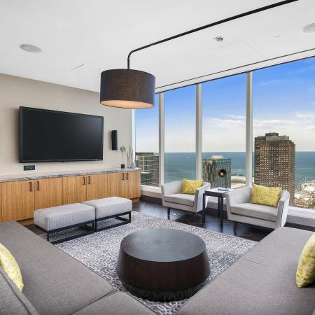 Sky lounge media room with a flat-screen TV and floor-to-ceiling windows with a city view