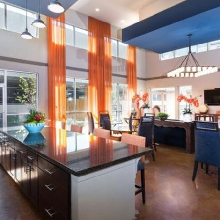 Beautiful clubroom with modern seating and large chandelier and floor to ceiling windows. and community kitchen with large island