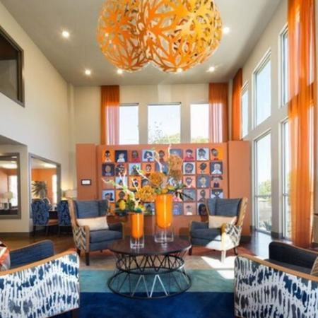 Beautiful clubroom with modern seating and large chandelier and floor to ceiling windows.