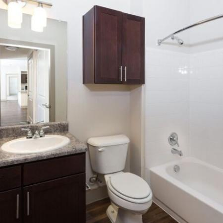 Bathroom with espresso cabinets with chrome fixtures, and soaking tub