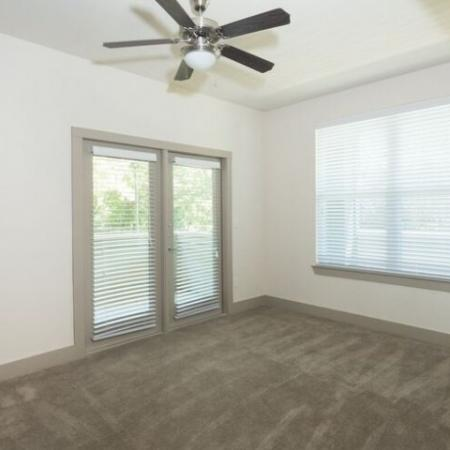 Living room with carpet throughout, ceiling fan and large windows