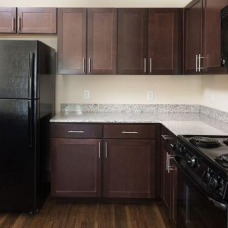 Beautiful kitchen with espresso cabinets, light grey countertops, and black appliance, and large kitchen island and hardwood style flooring
