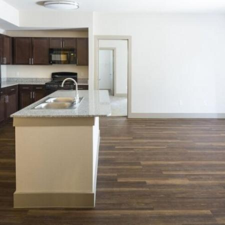 Beautiful kitchen with espresso cabinets, light grey countertops, and black appliance, and large kitchen island, and hardwood style flooring