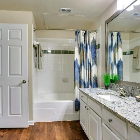 Bathrooms with granite counter tops and hard wood flooring