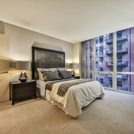 Furnished model bedroom with queen size bed and city view