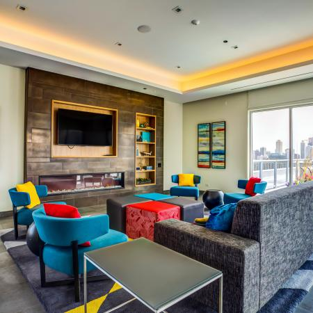 Furnished rooftop party room featuring a fireplace, flat-screen TV and city views