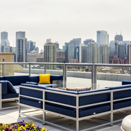 Large rooftop deck with panoramic skyline views and a lounge area