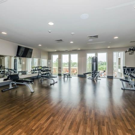 Fitness center with exercise equipment, mirrors and high ceilings