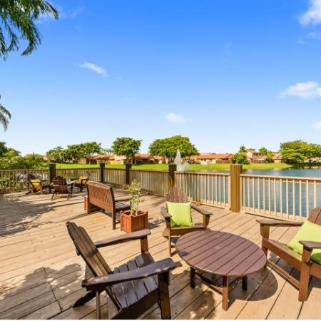 Outdoor deck with lounge chairs and coffee tables on a lake