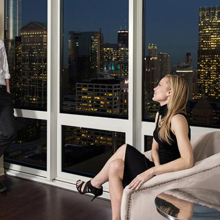 Man and woman sitting at window with magnificent city views