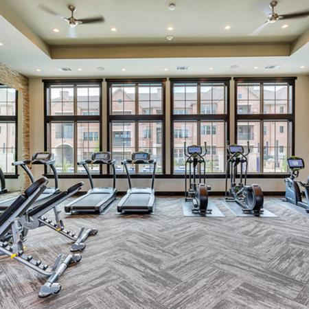 Fitness center with strength training and smart technology cardio machines, three treadmills, two elliptical and one bike
