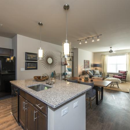 View From Large Open Kitchen with Island into Dining and Living Room with Wood Inspired Flooring and Designer Lighting Package | Nashville Tennessee Apartments for Rent | 909 Flats