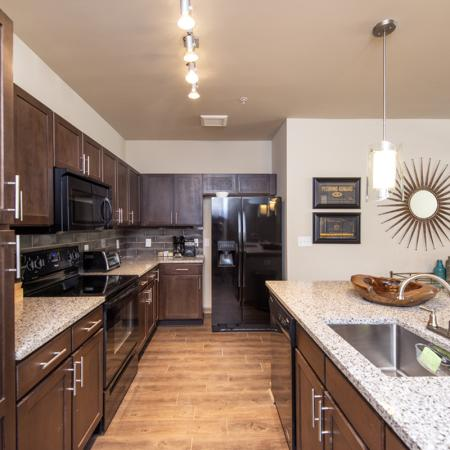 Spacious Kitchen with Quartz Countertops, Pendant Lighting and Black Appliances | Nashville Apartments | 909 Flats