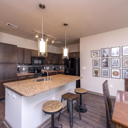 View into Kitchen with Bar Seating and Pendant Lighting | Nashville Apartments | 909 Flats