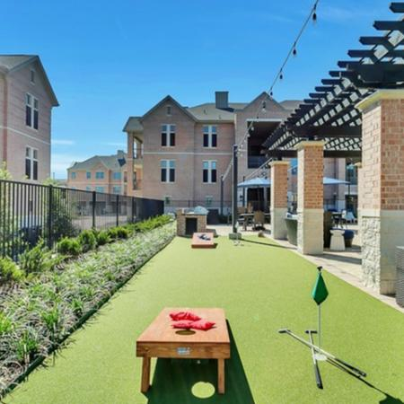outdoor game court yard, with mini golf and corn hole.
