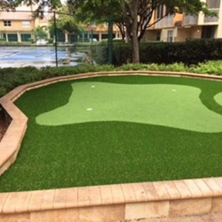 Putting green with 3 holes and tennis court in background