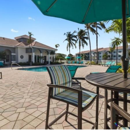 Swimming pool courtyard with chaise lounge chairs and covered entry into the clubhouse and leasing office