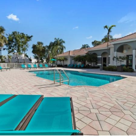 Swimming pool surrounded by chaise lounge chairs and patio tables with umbrellas