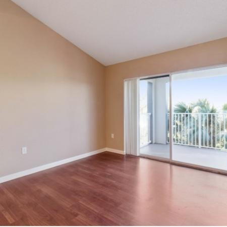 Unfurnished living room with wood floors, vaulted ceiling, and sliding glass balcony doors