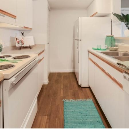Apartment parallel style kitchen with wood floors, pantry, white cabinets and drawers, and a white appliance package including a refrigerator, dishwasher, oven and four burner stove top combo, and a stainless steel two basin sink