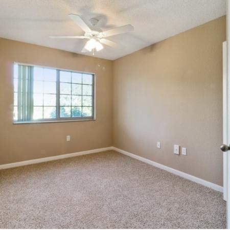Unfurnished apartment den with double door entry, carpet flooring, and a ceiling fan