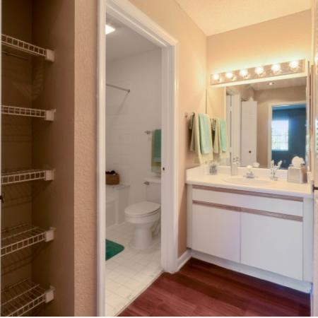 Apartment bathroom with a sink area that includes white cabinets underneath, wood flooring, a large mirror with bulb lighting, and a doored off room for the bathtub and toilet with tile floors