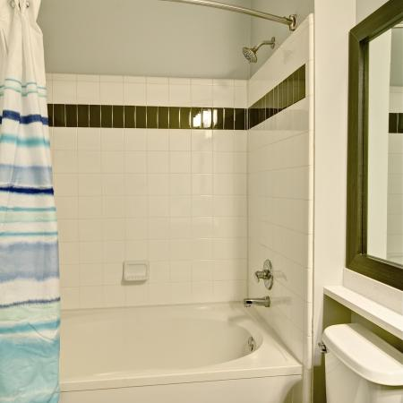 Narrow view of bathroom with curved shower rod and framed mirror