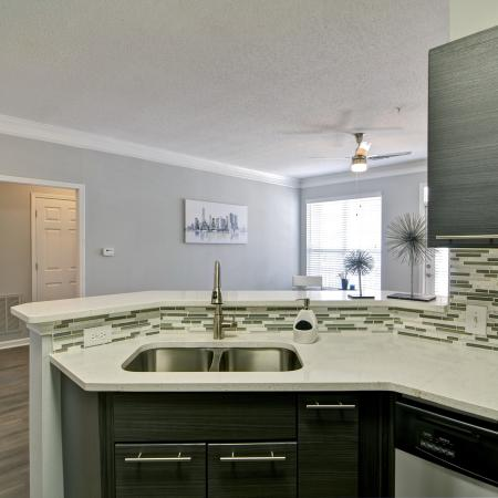 View from kitchen with double bowl sink and pull down faucet into open living area with ceiling fan