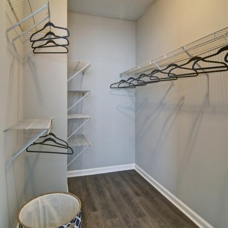 Large walk in closet with 3 wire shelves for hanging clothes and 4 wire shelves for organization