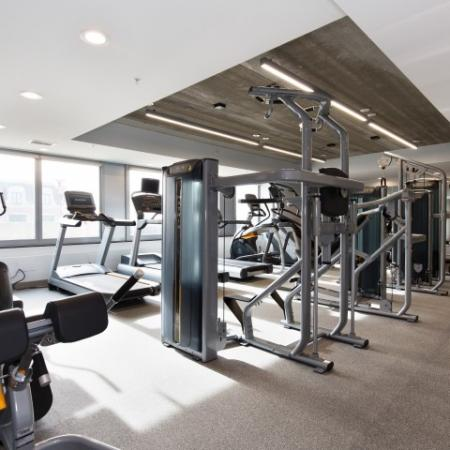 Renovated fitness center with exercise equipment and concrete ceilings