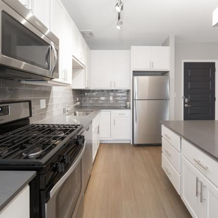 Upgraded kitchen with gas stove, stainless steel appliances, island, and hardwood floors