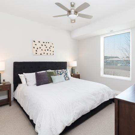 Furnished bedroom model with ceiling fan and carpeted floors