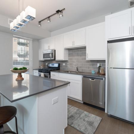 Upgraded kitchen with stainless steel appliances, island and harwood floors