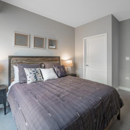 Furnished bedroom with queen size bed, nightstands and lamps