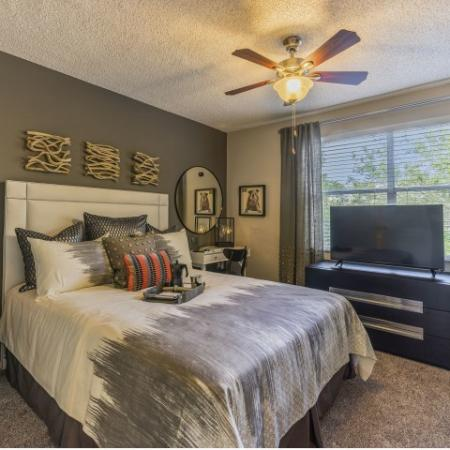 Bedroom with carpeting, queen sized bed, large window, ceiling fan, grey accent wall, dresser with television and nightstands