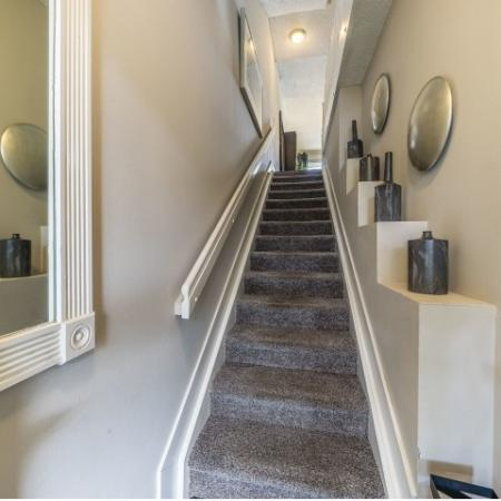 Carpeted stairs leading up to first floor of apartment with decorative ledges on right side and handrail on left side