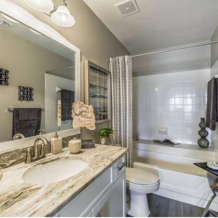 Bathroom with tub/shower combo, single sink with granite countertop, wood floor, and large framed mirror