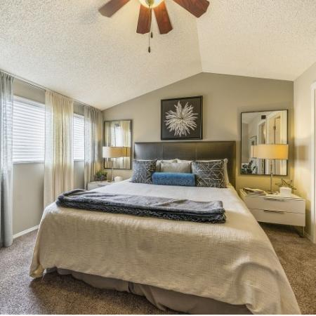 Carpeted bedroom with queen sized bed, two large windows, 2 nightstands and bathroom to the right