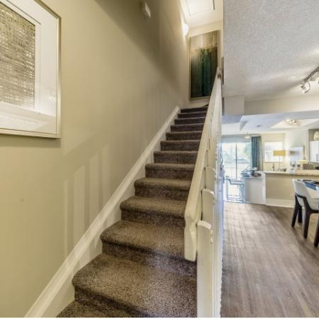 Carpeted stair leading to 2nd floor with handrail on right. Dining area with wood floors, kitchen and living area with sliding patio doors to the right of the stairs