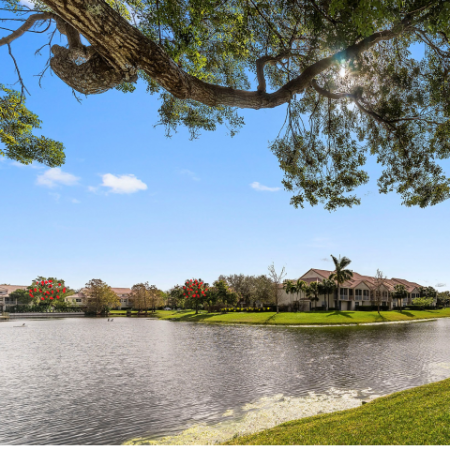 Large pond with landscaping and apartment community