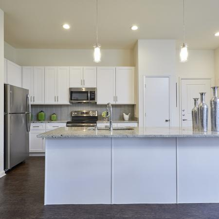 MODERN WHITE CABINETRY WITH BRUSHED NICKEL HARDWARE,CHEF -INSPIRED KITCHENS WITH GRANITE COUNTERS, HARDWOOD-INSPIRED FLOORING.STAINLESS STEEL APPLIANCES.
