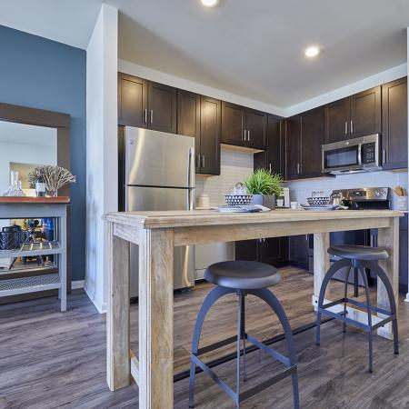 MODERN CABINETRY WITH BRUSHED NICKEL HARDWARE,CHEF -INSPIRED KITCHENS WITH GRANITE COUNTERS, HARDWOOD-INSPIRED FLOORING.STAINLESS STEEL APPLIANCES.